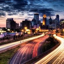 Downtown Minneapolis skyline and light trails on road