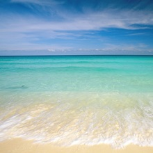 Clear blue water and wispy clouds along the beach at Cancun, Mexico