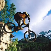 Man jumping on bike with Ha Ling Peak in the background, Alberta, Canada