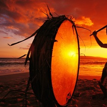 Native Hawaiian beating drum on Makena beach at sunset, Maui, Hawaii