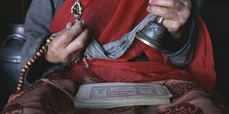 A Buddhist lama with prayer book, prayer beads and dorge