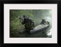 Navy SEALs navigate the waters in a folding kayak during jungle warfare operations