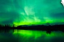 Green Aurora Borealis over small pond in Kluane National Park, Yukon Territory, Canada
