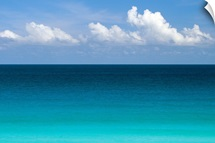 Clear blue water and white puffy clouds along the beach at Cancun