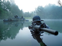 Special operations forces combat diver transits the water armed with an assault rifle