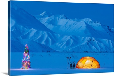 A Backpacking Tent Lit Up At Twilight With A Christmas Tree Next To It