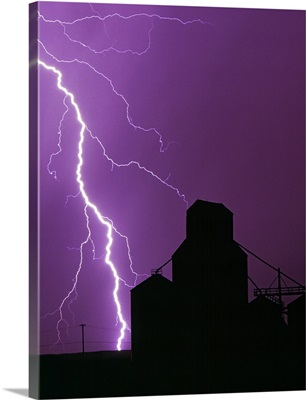 A bolt of lightning lights up the night sky during a storm silhouetting a grain elevator