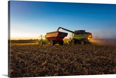 A farmer augers yellow grain corn from his combine into a grain wagon at night in Iowa
