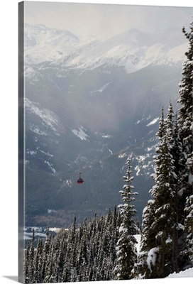 A Red Cable Car Riding Over Snow Covered Forest, Whistler, BC, Canada