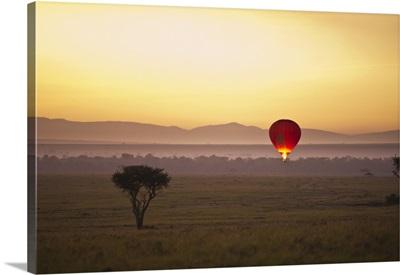 A Red Hot Air Balloon Against The Glowing Sky At Sunset; Masai Mara Kenya, Africa