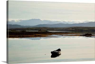 A rowboat sits in a tranquil lake with hills in the background, Ireland