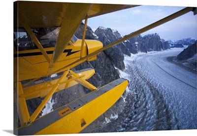 A Super Cub Floatplane Flies Over The Ruth Glacier Valley, Southcentral, Alaska