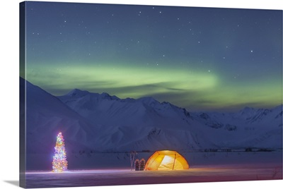 A tent and decorated Christmas tree glow under the Northern Lights