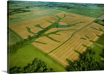 Aerial view of newly planted springtime agricultural fields and green grassy waterways