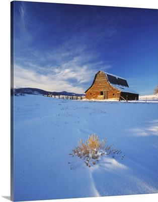 An old rustic weather worn western barn in snow