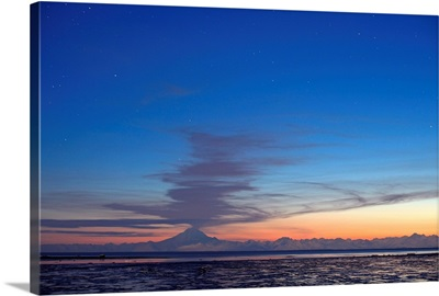 Ash cloud rises from Mt. Redoubt at sunset during low tide near Ninilchik, Alaska