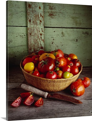 Basket of heirloom tomatoes of various varieties with a slicing knife and sliced tomato