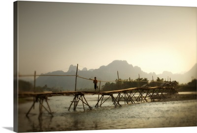 Boy Running Across Wooden Bridge With Mountains In The Background; Vang Vieng, Laos
