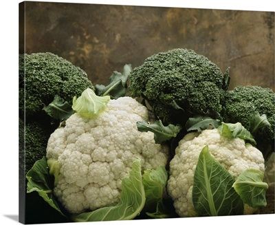 Broccoli crowns and cauliflower heads on marble