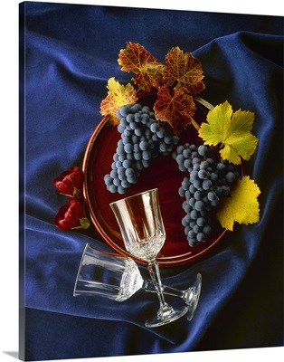 Cabernet Sauvignon wine grape clusters and leaves with wine glasses and flowers