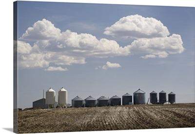 Calgary, Alberta, Canada; A Row Of Grain Bins In A Tilled Field