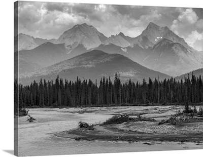 Canadian rocky mountains with a forest and a flowing river in the foreground