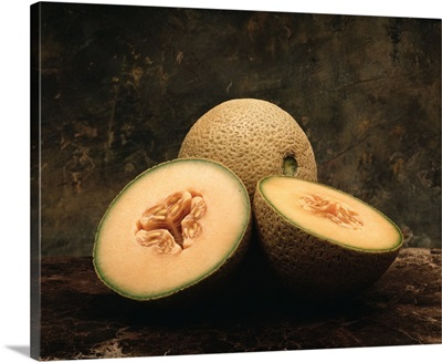 Cantaloupes on marble, one sliced in half