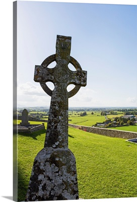Celtic cross on grassy hill with stone wall under blue sky, Cashel, Ireland