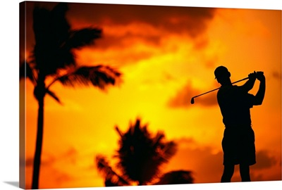 Close-Up Of Man Swinging, Silhouetted In Orange Skies, Palms Hazy In Background