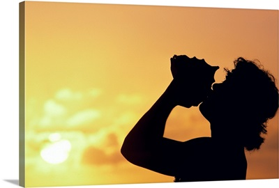 Conch Shell Blower On Cliff, Silhouetted At Sunset