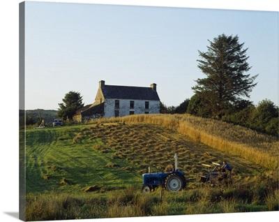 County Cork, Ireland; Farmer On Tractor Harvesting Field