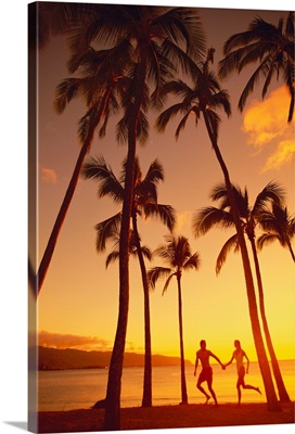 Couple Runs Together Holding Hands Under Palm Trees At Sunset