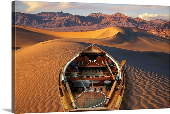 drift boat resting on sand dunes in death valley national park wall