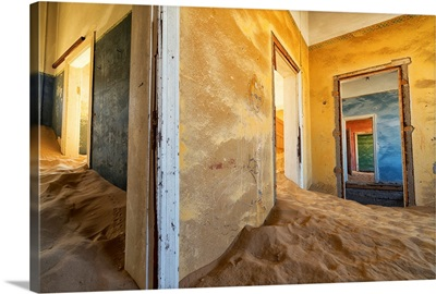 Drifting sand fills the rooms of a colourful abandoned house, Kolmanskop, Namibia