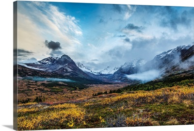 Fall landscape of tundra and willows with snow covered Chugach Mountains, Alaska