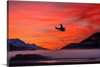 Floatplane takes off from Juneau as the fog begins to clear at sunrise, Southeast Alaska