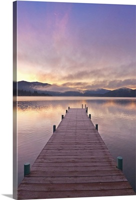 Footprints leading down a frost covered dock at sunrise on Lake Whatcom during Winter