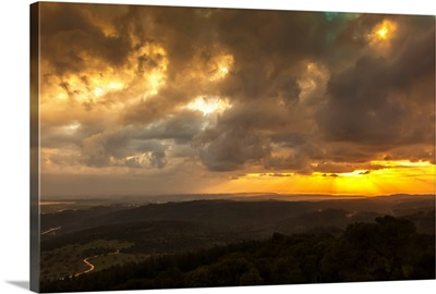 Golden sunset with glowing clouds and silhouetted landscape, Israel