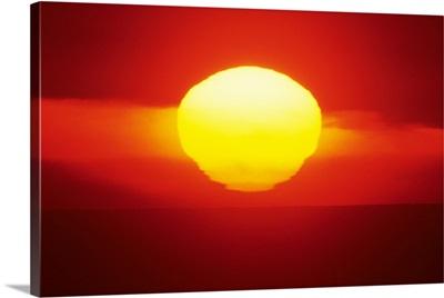 Gorgeous Sun Setting In Bright Orange Sky Over Ocean
