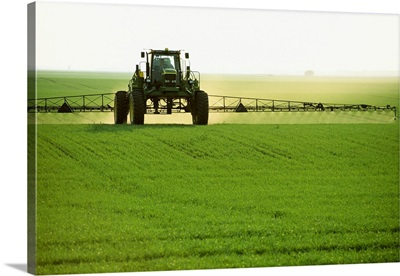 Ground application of herbicide on early growth oats, near Niverville, Manitoba, Canada