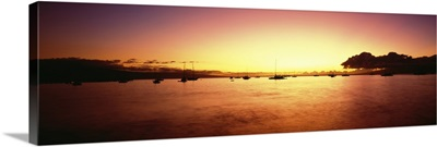 Hawaii, Maui, Boats In Ocean Near Wharf Sihouetted Against Colorful Sunset