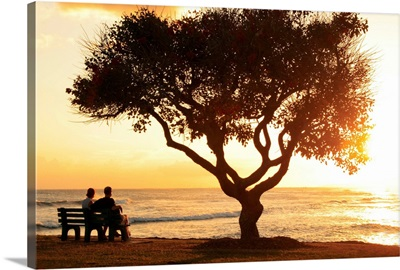 Hawaii, Oahu, Beautiful Sunset Over The Ocean With A Couple Sitting On A Bench