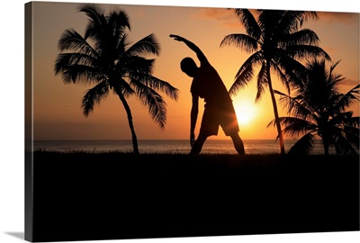 Hawaii, Oahu, Silhouette Of Man Stretching Near The Beach As The Golden Sunsets