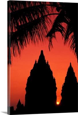 Indonesia, Java, Prambanan, Silhouette Of Temple At Sunset With Palm Tree