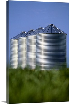 Large grain storage bins next to a grain field, near Carey, Manitoba, Canada