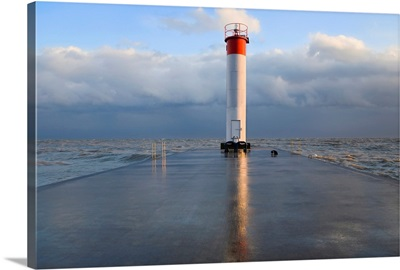 Lighthouse reflected on a wet pier on a stormy day by Lake Ontario, Whitby, Ontario