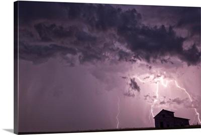 Lightning strikes as it approaches an old abandoned farm house, Val Marie, Saskatchewan