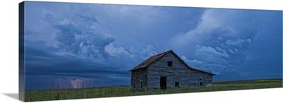 Lightning strikes over the prairies and abandoned farm house, Val Marie, Saskatchewan