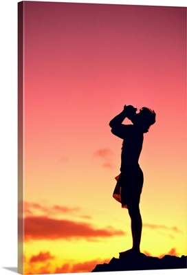 Man Silhouetted At Sunset Blowing A Conch Shell