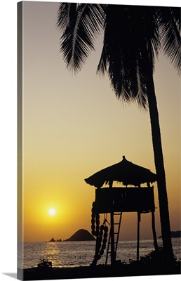 Mexico, Ixtapa Coast, Beach Bungalow And Palm Tree Silhouette At Sunset